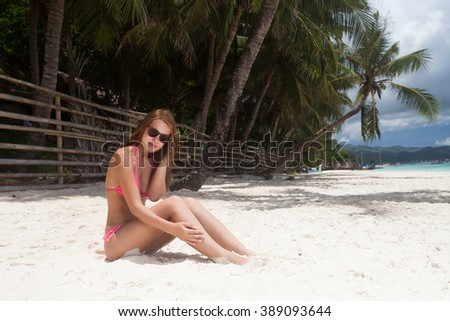 Young beautiful woman lying on the sand at the beach - stock photo