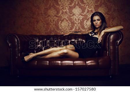 Young beautiful woman lying on the sofa - stock photo