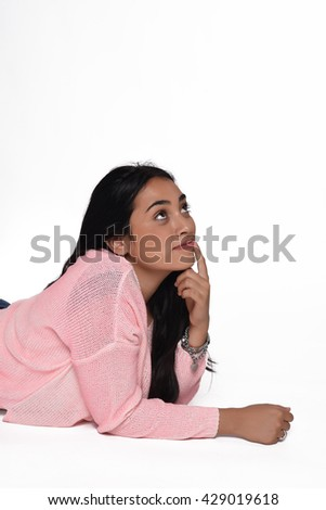 Young beautiful woman lying thoughtful. Isolated white background. - stock photo