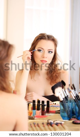 Young beautiful woman making make-up near mirror - stock photo