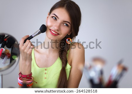 Young beautiful woman making make-up near mirror,sitting at the desk - stock photo