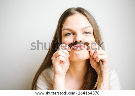 Young beautiful woman making mustache with pouching lips on white background - stock photo