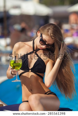 Young beautiful woman making water splash in sexy bikini at the pool.Enjoying summer.Young slim fit tanning woman having fun near poll and making water splash with her sexy legs. Vacation mood. - stock photo