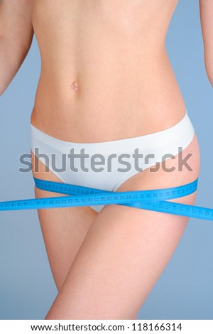 Young Beautiful Woman Measuring Her Hip. Perfect Slim Body