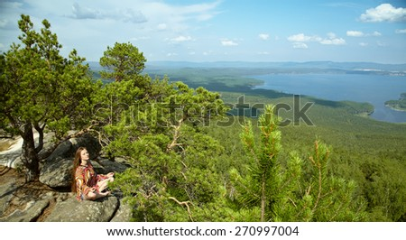 Young beautiful woman meditating at the mountains. relaxation outdoors. nature freedom and inspiration - stock photo