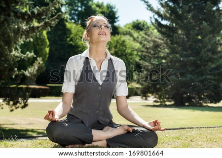 Young beautiful woman meditating in the park - stock photo