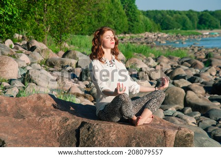 Young beautiful woman meditating near the sea