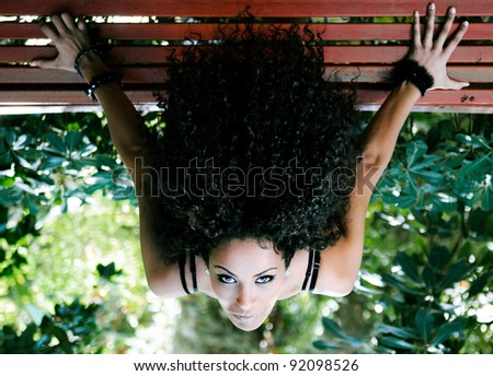 Young beautiful woman, model of fashion,  siting on bench in park - stock photo