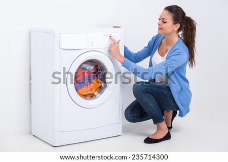 Young beautiful woman near the washing machine on a white background.