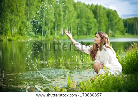 Young beautiful woman near water smiling
