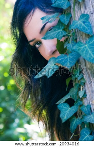 Young beautiful woman observing behind leaves. - stock photo