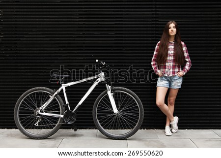 Young beautiful woman on a bicycle ride - stock photo