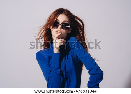 Young beautiful woman on a light background in a strict jacket and black glasses. Expressive model. Model hamming
