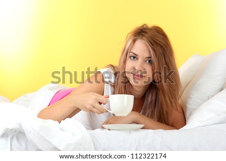 young beautiful woman on bed with cup of coffee on yellow background
