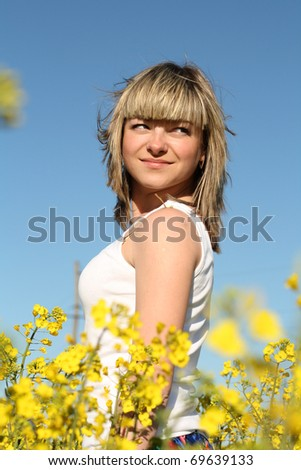 young beautiful woman on blooming field in summer - stock photo