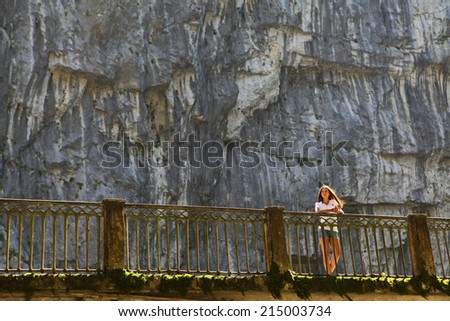 Young beautiful woman on bridge in Caucasus mountains to the way to Ritza lake - stock photo