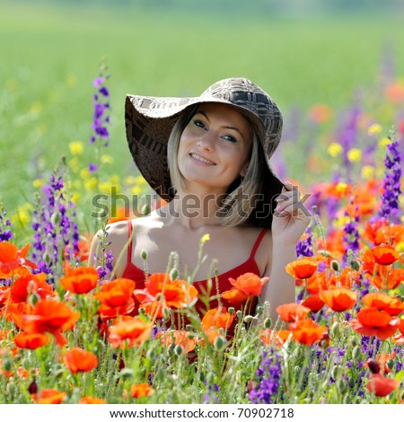 young beautiful woman on flower field in summer - stock photo