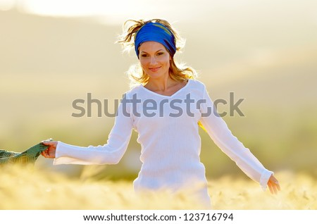 young beautiful woman on golden cereal field in summer - stock photo