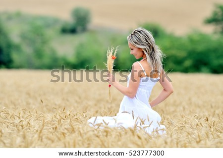 young beautiful woman on golden field in summer