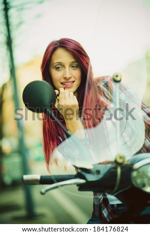 Young beautiful woman on motorcycle fixing her make up. - stock photo