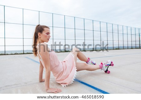 Young beautiful woman on roller skates posing on the playground