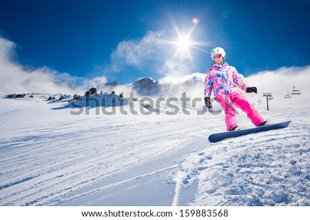 Young beautiful woman on snowboard sliding downhill in mountains with sun coming between low clouds - stock photo