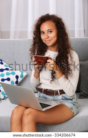 Young beautiful woman on sofa using laptop and drinking coffee in the room - stock photo