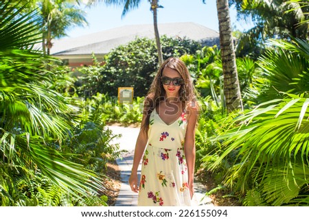 Young beautiful woman on summer vacation at lush garden - stock photo