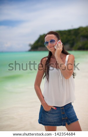 Young beautiful woman on the beach talking on her phone - stock photo