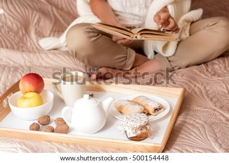 Young beautiful woman on the bed with a book. Happy woman resting at home on the bed. Cozy. Autumn breakfast. Young woman sitting on the bed reading a book and eating breakfast. Bakery products.
