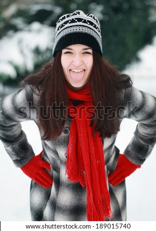 Young beautiful woman outdoor put out one's tongue in winter