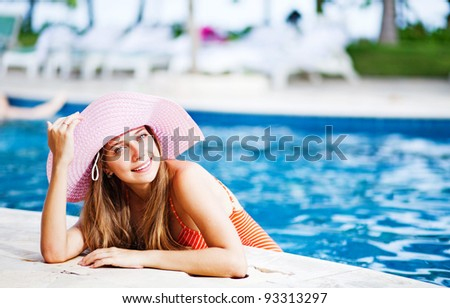 Young beautiful woman outdoors looks outside the swimming pool - stock photo