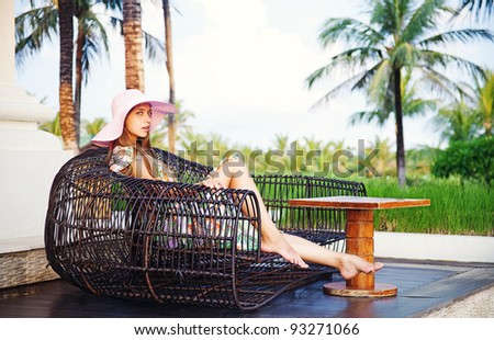 Young beautiful woman outdoors sitting in original restaurant - stock photo