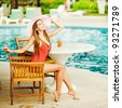 Young beautiful woman outdoors sitting on the chair near swimming-pool - stock photo