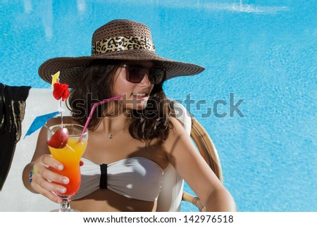 Young beautiful woman outdoors sitting on the couch near swimming-pool drinking a fresh cocktail - stock photo