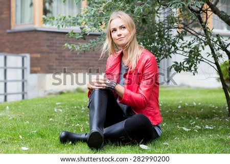 Young beautiful woman outdoors sitting on the grass and smiling. - stock photo