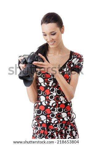 Young beautiful woman photographed on reflex camera, isolated on white background. - stock photo