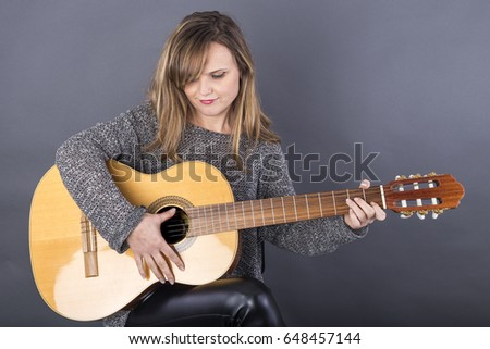 Young beautiful woman playing an acoustic guitar isolated over gray background