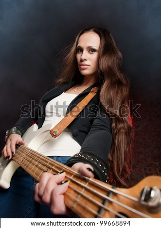 Young beautiful woman playing the guitar on the scene - stock photo