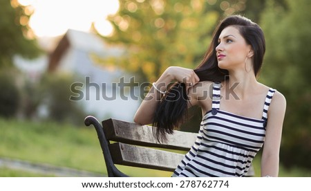 Young beautiful woman playing with her long hair, outdoors - outside. Pretty hispanic alone girl posing on bench in a park looking to side, profile - sideways concept - stock photo