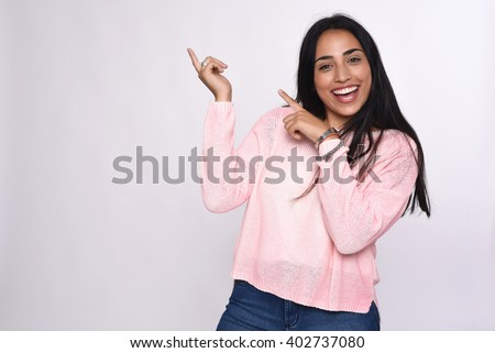 Young beautiful woman pointing at white background. - stock photo