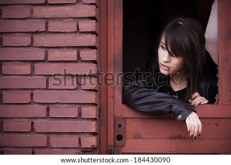 Young beautiful woman portrait on rusty window - stock photo