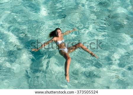 Young beautiful woman posing in the sea with white bikini. Vacation concept. - stock photo