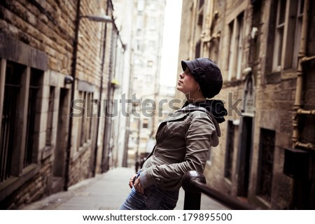 Young beautiful woman posing on urban alleyway - stock photo