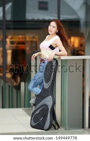 Young beautiful woman posing outdoor with her guitar gig bag, model is Thai Ethnic.