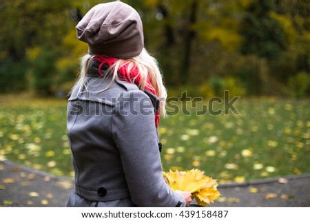Young beautiful woman posing outside at fall time