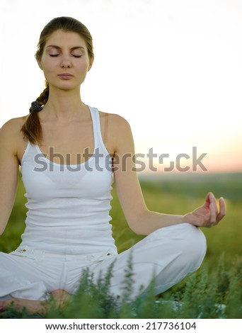 Young Beautiful Woman Practices Yoga on the Meadow. Active Lifestyle