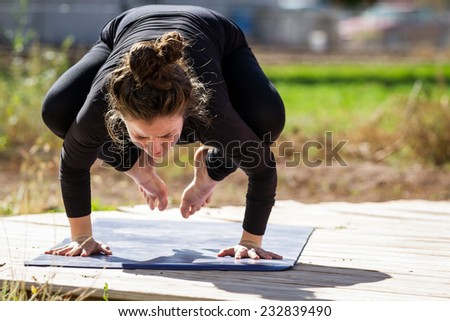 young beautiful woman practicing the art of yoga on an outdoors setting - stock photo
