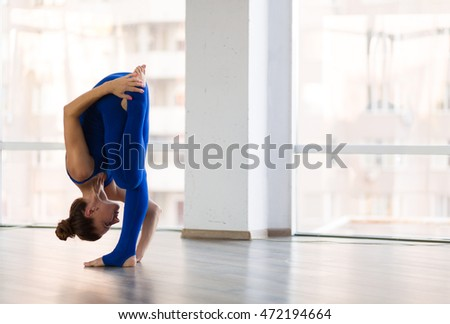 Young beautiful woman practicing yoga in a studio
