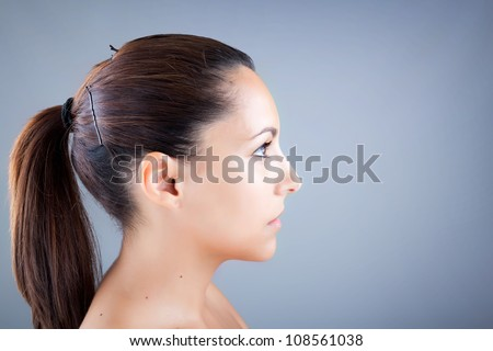 Young beautiful woman profile portrait on grey background - stock photo
